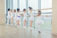 Groupe de sept petites ballerines se tenant dans la rangée et la pratique Photographie stock libre de droits