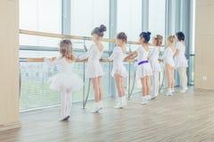 Groupe de sept petites ballerines se tenant dans la rangée et le ballet de pratique utilisant le bâton sur le mur Photographie stock