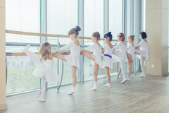 Groupe de sept petites ballerines se tenant dans la rangée et le ballet de pratique utilisant le bâton sur le mur Photo stock