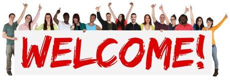 Groupe de signe bienvenu de jeunes ethniques multi tenant la bannière Images libres de droits