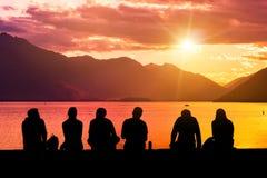Groupe de silhouette des jeunes s'asseyant sur la plage Image stock