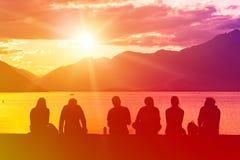 Groupe de silhouette des jeunes s'asseyant sur la plage Photos libres de droits