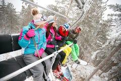 Groupe de skieur d'amis s'asseyant à l'ascenseur de chaise de ski au beau su Photographie stock libre de droits