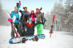 Groupe de skieurs et de surfeurs d'amis ayant l'amusement sur bloqué par la neige Photo libre de droits