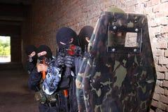 Groupe de soldat déménageant derrière l'écran protecteur tactique image libre de droits