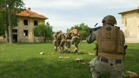 Groupe de soldats avec des manoeuvres tactiques obtenant près de l'objectif dans le secteur de conflit banque de vidéos