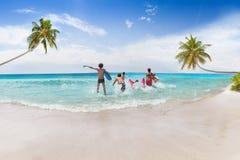 Groupe de sortes fonctionnant dans la mer sur la plage de sable Photo stock