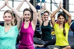Groupe de sourire convenable faisant le yoga Images stock