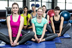 Groupe de sourire convenable faisant le yoga Image stock