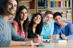 Groupe de sourire d'étudiants dans une bibliothèque Image stock