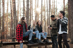 Groupe de sourire d'amis s'asseyant dehors dans la forêt Images stock