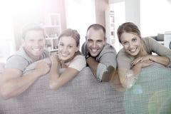 Groupe de sourire d'amis s'asseyant sur un sofa Photographie stock libre de droits