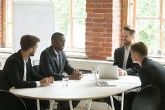 Groupe de sourire satisfait de quatre hommes d'affaires parlant riant du mee Image stock