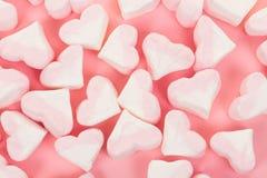 Groupe de sucrerie rose et blanche en forme de coeur de guimauve sur un fond rose Images libres de droits