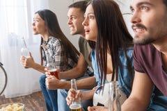 Groupe de supporters d'amis observant le jeu intéressant de match de football Image libre de droits