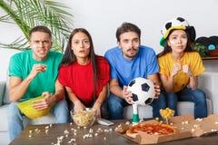 Groupe de supporters d'amis regardant la rencontre concentrée dans des chemises colorées Image stock