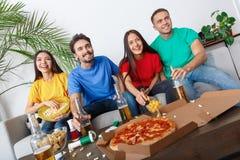 Groupe de supporters d'amis regardant la rencontre dans des chemises colorées concentrées Image stock