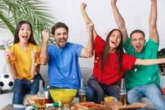 Groupe de supporters d'amis regardant la rencontre dans des chemises colorées encourageant l'équipe excitée Photos libres de droits
