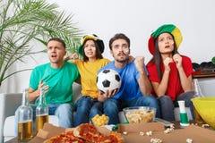 Groupe de supporters d'amis regardant la rencontre dans des chemises colorées encourageant l'équipe nerveuse Photo libre de droits