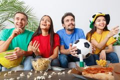 Groupe de supporters d'amis regardant la rencontre dans des chemises colorées gaies Photographie stock libre de droits