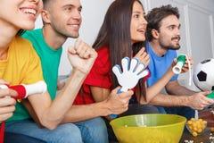 Groupe de supporters d'amis regardant la rencontre dans des chemises colorées jugeant des personnes en gros plan Images libres de droits