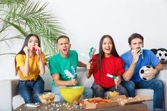 Groupe de supporters d'amis regardant la rencontre dans des chemises colorées tenant des personnes Photographie stock