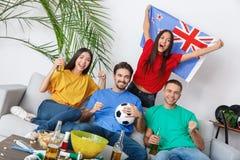 Groupe de supporters d'amis regardant la rencontre dans la fille colorée de chemises tenant le drapeau de la Nouvelle Zélande Images libres de droits