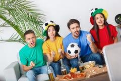 Groupe de supporters d'amis regardant la rencontre dans l'équipe colorée de soutien de chemises Photos stock