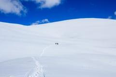 Groupe de surfeurs montant la montagne de neige et le ciel bleu Photographie stock