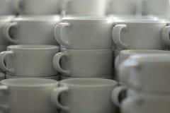 Groupe de tasses en céramique blanches vides pour le café ou le thé dans un hôtel images libres de droits