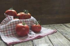Groupe de tomates dans le panier avec le torchon sur la table en bois Images libres de droits