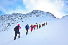 Groupe de touristes à s'élever sur un passage de montagne neigeux Images stock