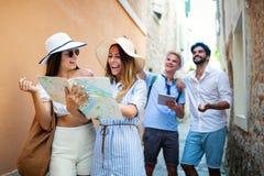 Groupe de touristes d'amis avec la carte dans la vieille ville des vacances photo stock