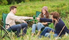 Groupe de touristes de sourire buvant de la bière dans le camping Images stock