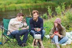 Groupe de touristes de sourire faisant cuire la nourriture dans le camping Images libres de droits