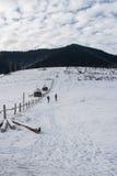 Groupe de touristes escaladant la colline couverte de neige Images libres de droits