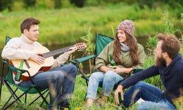 Groupe de touristes jouant la guitare dans le camping Image libre de droits