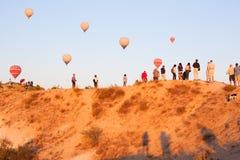 Groupe de touristes observant le ballon voler sur la montagne photo stock