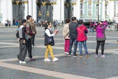 Groupe de touristes orientaux d'aspect asiatique sur la place de palais de St Petersburg sur le fond de l'ermitage, Russie, images libres de droits