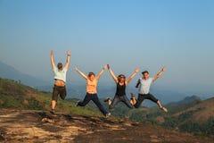 Groupe de touristes sautant sur la montagne Images stock