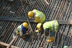 Groupe de travailleurs de la construction fabriquant la barre en acier de renfort Images stock