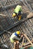 Groupe de travailleurs de la construction fabriquant la barre en acier de renfort Photo libre de droits