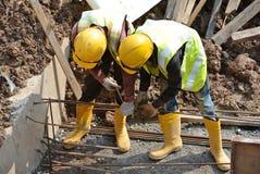 Groupe de travailleurs de la construction fabriquant la barre en acier de renfort de faisceau au sol Photo libre de droits