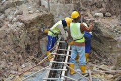 Groupe de travailleurs de la construction fabriquant la barre en acier de renfort de faisceau au sol Photos stock