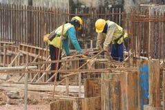 Groupe de travailleurs de la construction fabriquant la barre en acier de renfort de faisceau au sol Image stock