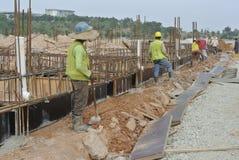 Groupe de travailleurs de la construction installant le coffrage de faisceau au sol Photos libres de droits