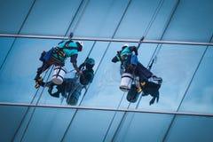 Groupe de travailleurs nettoyant le service de fenêtres sur le bâtiment ayant beaucoup d'étages Images stock