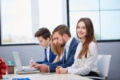 Groupe de travailleurs travaillant dans le bureau, fille dans des écouteurs regardant l'appareil-photo et le sourire image stock