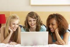 Groupe de trois adolescentes à l'aide de l'ordinateur portatif dans Bedro Photo stock