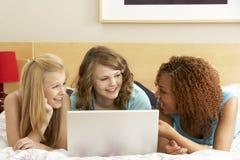 Groupe de trois adolescentes à l'aide de l'ordinateur portatif dans Bedro Photographie stock